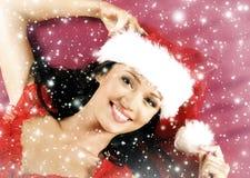 Retrato de uma mulher que coloca em um chapéu do Natal Fotografia de Stock Royalty Free