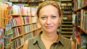Retrato de uma mulher que está na biblioteca Estantes da biblioteca no fundo 4k, lento-movimento filme