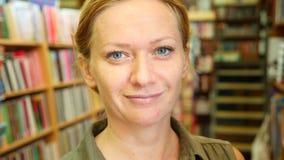 Retrato de uma mulher que está na biblioteca Estantes da biblioteca no fundo 4k, lento-movimento vídeos de arquivo