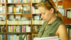 Retrato de uma mulher que está na biblioteca Estantes da biblioteca no fundo 4k, lento-movimento video estoque