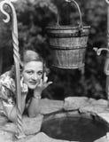 Retrato de uma mulher que inclina-se no bem com seu dedo cruzado (todas as pessoas descritas não são umas vivas mais longo e nenh Fotografia de Stock