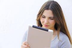 Retrato de uma mulher que lê um ebook da tabuleta Fotos de Stock Royalty Free