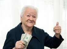 Retrato de uma mulher que mantem o dinheiro disponivel e que mostra sim o sinal imagens de stock