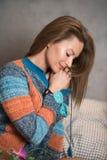 Retrato de uma mulher que senta-se em uma cama e que veste uma camiseta Fotografia de Stock Royalty Free