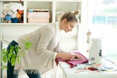 Retrato de uma mulher que trabalha com um teste padrão da costura fotos de stock