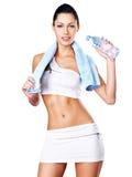 Retrato de uma mulher saudável com a garrafa da água e da toalha. Fotografia de Stock