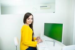 Retrato de uma mulher de sorriso bonita, trabalhando no computador com tela verde, em um ambiente do escrit?rio imagens de stock royalty free