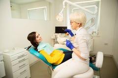 Retrato de uma mulher de sorriso, sentando-se na cadeira dental com o doutor no escrit?rio dental imagens de stock royalty free
