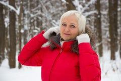 Retrato de uma mulher superior agradável na madeira da neve do inverno no revestimento vermelho Fotos de Stock
