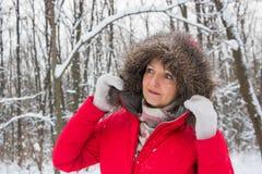 Retrato de uma mulher superior agradável na madeira da neve do inverno no revestimento vermelho Imagens de Stock Royalty Free