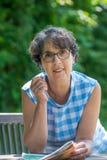 Retrato de uma mulher superior bonita no jardim Fotos de Stock