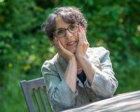 Retrato de uma mulher superior bonita no jardim Foto de Stock Royalty Free