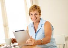 Retrato de uma mulher superior feliz que usa a tabuleta eletrônica em casa imagens de stock royalty free