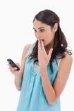 Retrato de uma mulher surpreendida que lê uma mensagem Imagens de Stock