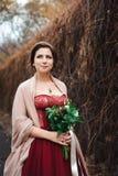 Retrato de uma noiva bonita em um vestido vermelho com um ramalhete do casamento em uma mão imagem de stock