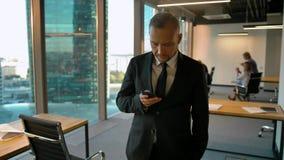 Retrato de uma posição atrativa do homem de negócios perto dos sms da janela e da escrita filme