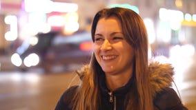 Retrato de uma posição da menina em uma rua da cidade da noite Mulher atrativa que anda através das ruas da cidade da noite 4k 60 filme