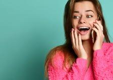Retrato de uma posição entusiasmado da moça isolado sobre o fundo violeta, falando no telefone celular imagens de stock