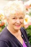 Retrato de uma senhora consideravelmente mais idosa com flores imagem de stock royalty free