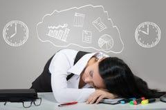 Retrato de uma senhora do escritório que dorme em seu local de trabalho fotografia de stock