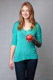 Retrato de uma senhora nova do gengibre na blusa de turquesa com um appl Imagem de Stock Royalty Free