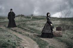 Retrato de uma senhora victorian no assento preto na estrada com seus bagagem e cavalheiro que andam abaixo da estrada imagem de stock royalty free