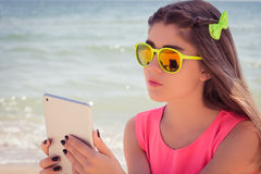 Retrato de un adolescente bonito en gafas de sol en una playa Fotografía de archivo libre de regalías
