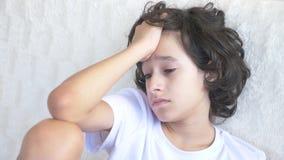 Retrato de un adolescente cansado triste que se sienta en el sofá 4K almacen de video