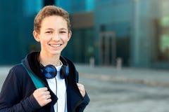 Retrato de un adolescente con los auriculares y la mochila al aire libre Copie el espacio imágenes de archivo libres de regalías