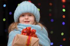 Retrato de un adolescente con un regalo en un azul del invierno hecho punto Imagenes de archivo