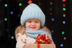 Retrato de un adolescente con un regalo en un azul del invierno hecho punto Fotos de archivo libres de regalías