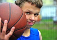 Retrato de un adolescente con un baloncesto Fotos de archivo libres de regalías