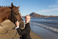 Retrato de un adolescente con un caballo preferido en el mar. Imagenes de archivo