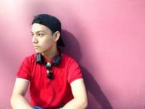 Retrato de un adolescente con un casquillo encendido y los teléfonos del oído Imagenes de archivo