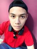 Retrato de un adolescente con un casquillo encendido y los teléfonos del oído Fotografía de archivo libre de regalías
