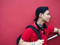 Retrato de un adolescente con un casquillo encendido y los teléfonos del oído Foto de archivo libre de regalías