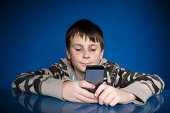 Retrato de un adolescente con un teléfono Imagen de archivo libre de regalías