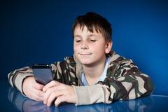 Retrato de un adolescente con un teléfono Fotografía de archivo libre de regalías