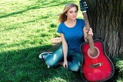 Retrato de un adolescente con una guitarra debajo de un árbol Imagenes de archivo