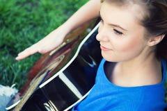 Retrato de un adolescente con una guitarra debajo de un árbol Imagen de archivo
