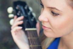 Retrato de un adolescente con una guitarra debajo de un árbol Fotos de archivo libres de regalías