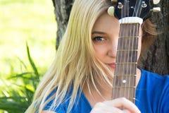 Retrato de un adolescente con una guitarra en el parque Imagen de archivo libre de regalías