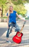 Retrato de un adolescente con una guitarra en el parque Fotos de archivo