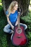 Retrato de un adolescente con una guitarra en el parque Fotos de archivo libres de regalías