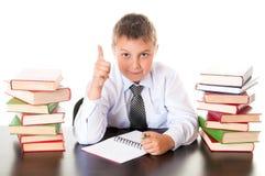 Retrato de un adolescente del muchacho en la escuela en biblioteca cerca de la pila de libros Inventada, vino la inspiración Cole foto de archivo