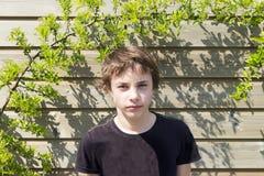 Retrato de un adolescente delante de la pared de madera Foto de archivo libre de regalías