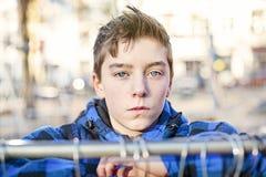 Retrato de un adolescente detrás de un carril de la ropa Fotografía de archivo libre de regalías