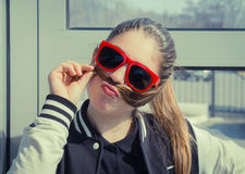 Retrato de un adolescente divertido en gafas de sol rojas Imagen de archivo