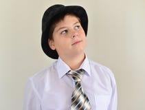 retrato de un adolescente en sombrero y lazo Foto de archivo libre de regalías