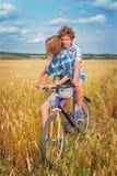 Retrato de un adolescente en una bicicleta que viaja en campo del centeno Foto de archivo